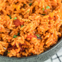 A close up of a bowl of food with rice meat and vegetables, with Spanish rice