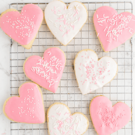 close up overhead shot of valentine sugar cookies with sprinkles on a rack