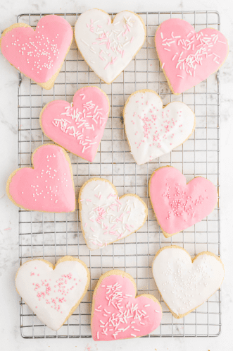 close up overhead shot of valentine sugar cookies withsprinkes on a rack