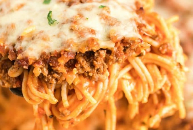slice of million dollar spaghetti being served from casserole dish
