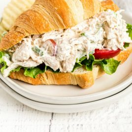 A close up of a sandwich on a plate, with Chicken and Salad