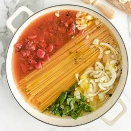 A bowl of food on a plate, with Pasta