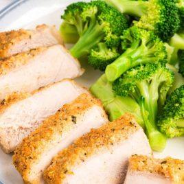 close up shot of slices of Parmesan Pork Chops served with broccoli