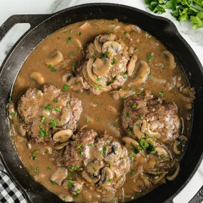 skillet with hamburger steaks frying in onions, mushrooms and gravy