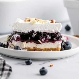 close up shot of a slice of blueberry delight topped with pecans and white chocolate curls on a plate