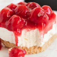 A close up of a slice of cake on a plate, with Cheesecake and Cherry