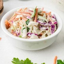 classic coleslaw topped with homemade salad dressing in a white bowl