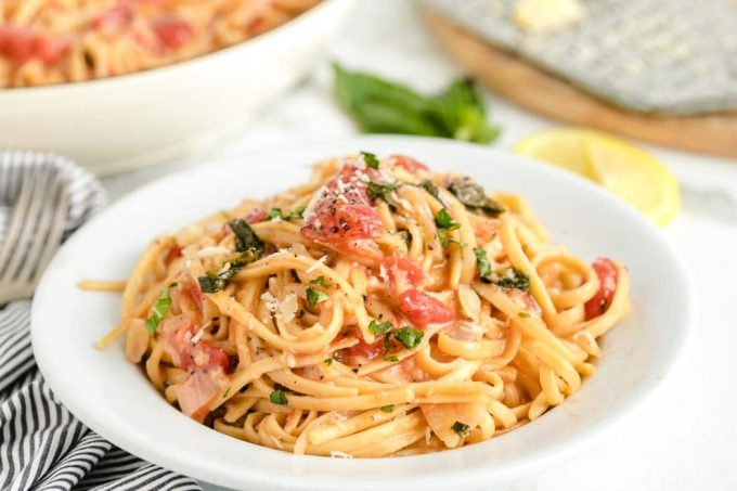 A bowl of pasta sits on a plate, with One pot pasta and Linguine