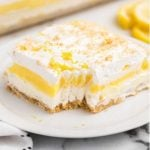close up shot of a slice of lemon lasagna with a piece taken out of it on a plate