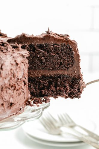 slice of layered chocolate mayonnaise cake being removed from cake stand