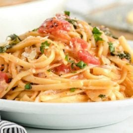 A bowl of one pot pasta topped with parsley on a plate