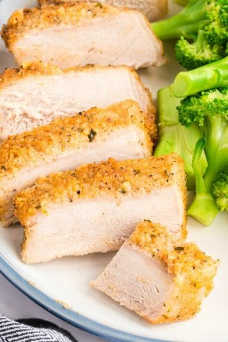 Parmesan pork chops sliced and on a plate with broccoli