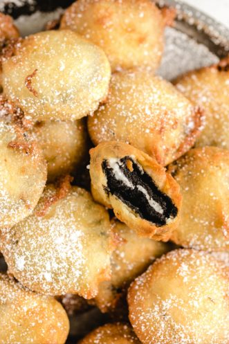 stack of deep fried oreos on plate with one cut open to reveal center