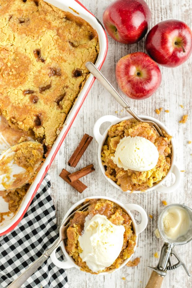 baking dish with caramel apple dump cake and two servings with ice cream from overhead