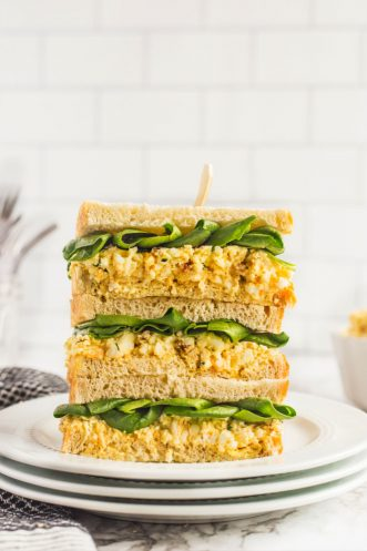 three egg salad sandwiches with spinach stacked on top of each other on a plate