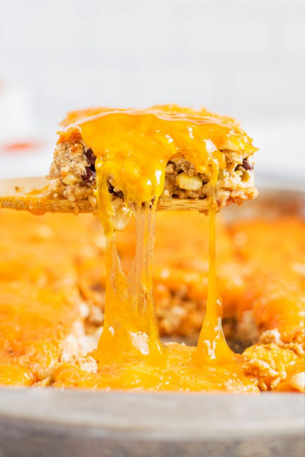 cheesy piece of mexican casserole on wooden spoon
