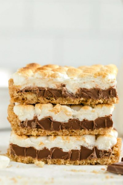 three smores bars with mini marshmallows stacked on top of one another