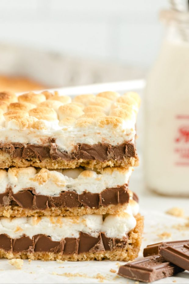three smores bars with mini marshmallows stacked on top of one another with milk in background