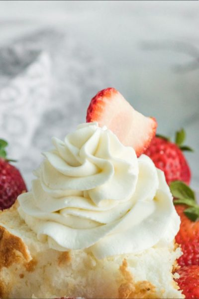 homemade whipped cream with strawberry garnish on shortcake