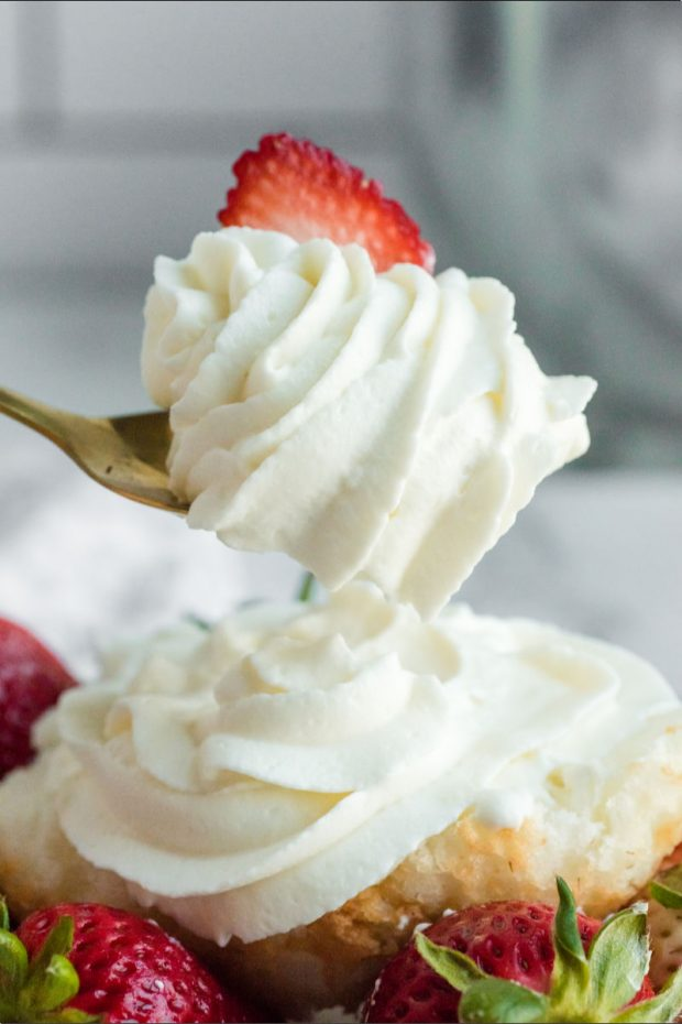 homemade whipped cream with strawberry garnish on spoon with shortcake under