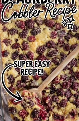close up overhead shot of blackberry cobbler in a baking dish with a wooden spoon