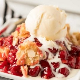 close up shot of a serving of Cherry Dump Cake topped with vanilla ice cream on a plate
