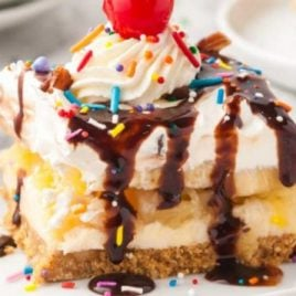 close up shot of a slice of banana split cake topped with chocolate syrup, sprinkles, whipped cream, and a cherry on a plate