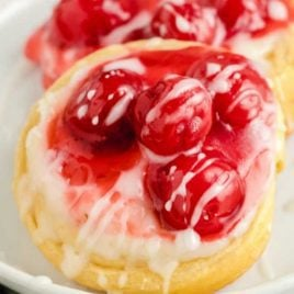 cherry danish topped with icing on a plate