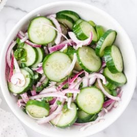 A bowl of salad on a plate, with Cucumber