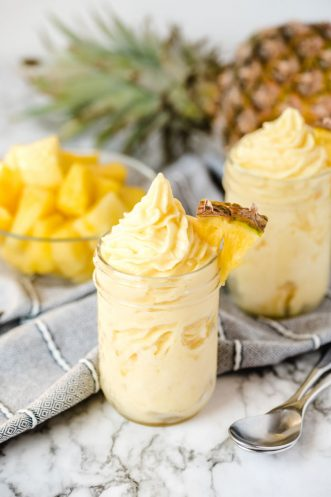 Dole whip in a glass with pineapple in background