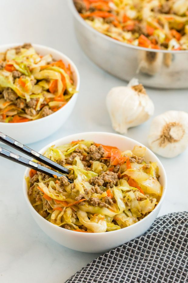 two bowls of egg roll in a bowl with skillet and chopsticks