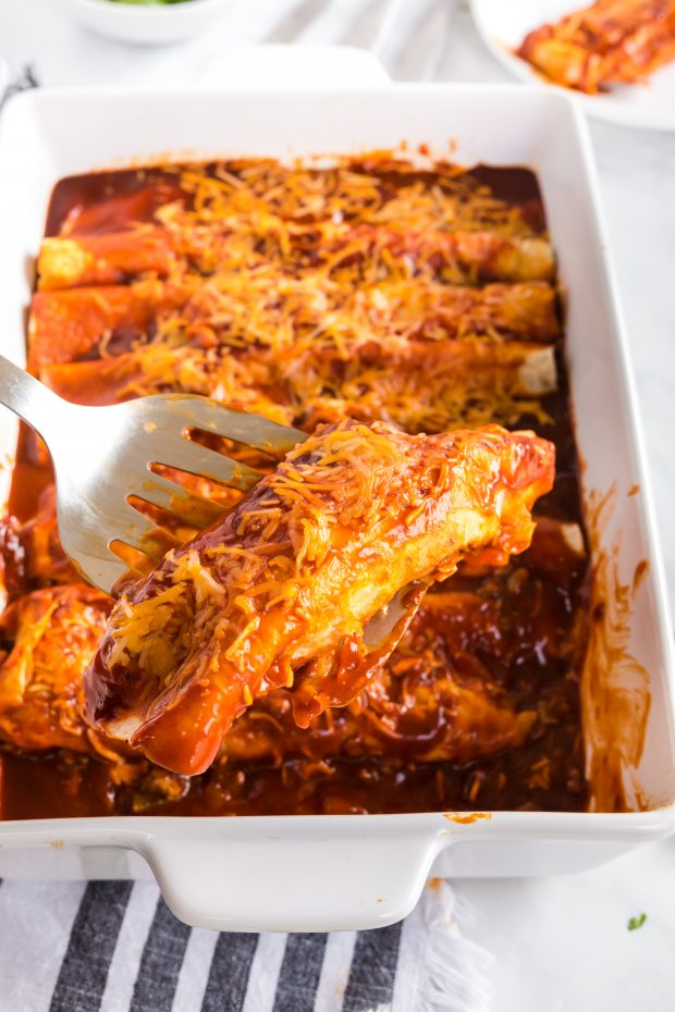 A tray of food on a plate, with Enchilada and Beef