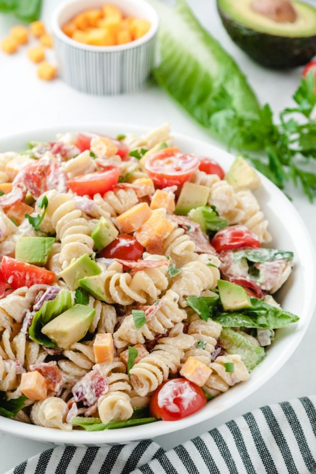 A bowl of salad on a plate, with Pasta and BLT