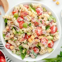 A bowl of salad on a plate, with BLT and Pasta