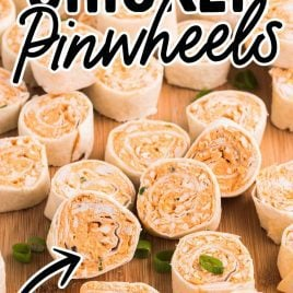 close up shot of Buffalo Chicken Pinwheels garnished with green onions on a wooden board