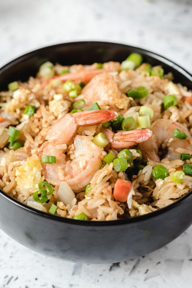 A bowl of food with rice and broccoli, with Shrimp and Fried rice