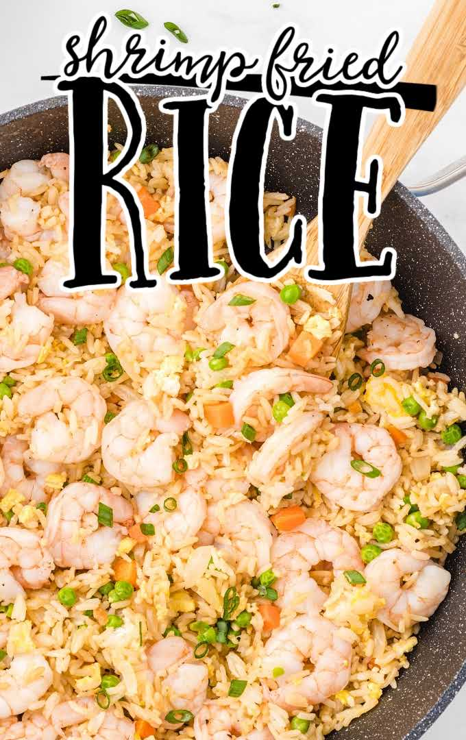 overhead shot of shrimp fried rice garnished with green onions in a pan with a wooden spoon