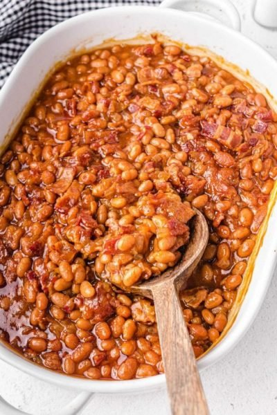 overhead shot of baked beans in a white baking dish being picked up with a wooden spoon