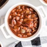 A bowl of food on a plate, with Baked beans