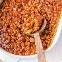 close up overhead shot of baked beans in a white baking dish being picked up with a wooden spoon