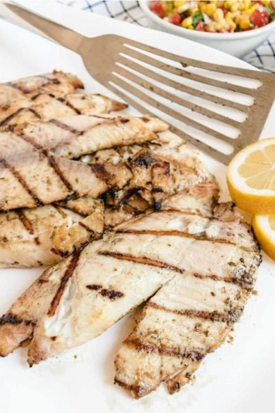 close up shot of grilled tilapia on a plate with slices of lemon and a spatula
