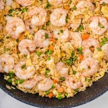 overhead shot of shrimp fried rice garnished with green onions in a pan