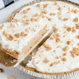 close up shot of No Bake Peanut Butter Pie topped with whipped cream and chopped peanuts with a slice being taken out of it