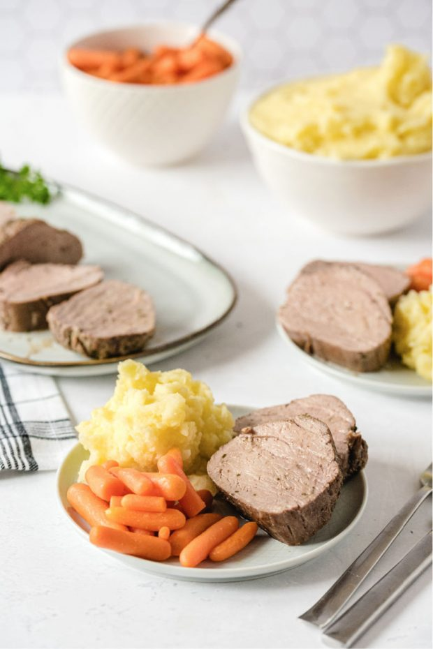 A bunch of food on a plate, with Pork tenderloin