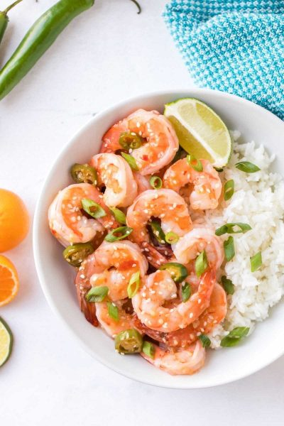 close up overhead shot of Spicy Garlic Shrimp served with white rice topped with green onions and a slice of lime in a bowl
