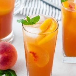 glasses of Sweet Peach Iced Tea served with peaches and ice topped with a mint