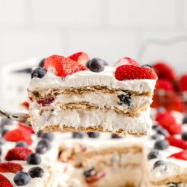 A close up of a decorated cake on a plate, with Berry and Icebox cake