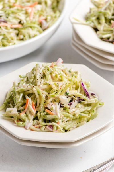 A bowl of salad on a plate, with Broccoli slaw