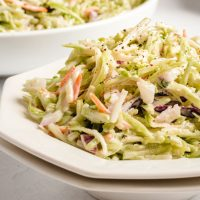 A bowl of pasta salad on a plate, with Broccoli slaw