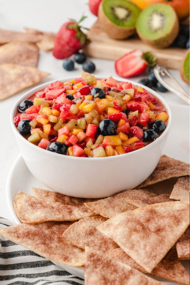 A plate of food on a table, with Salsa and Fruit